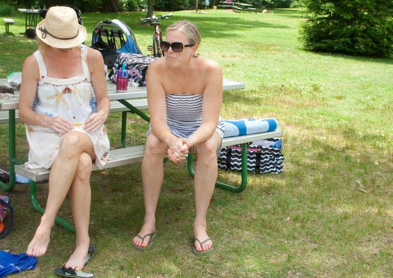 Dos mujeres que disfrutan de tiempo en un parque local foto de archivo