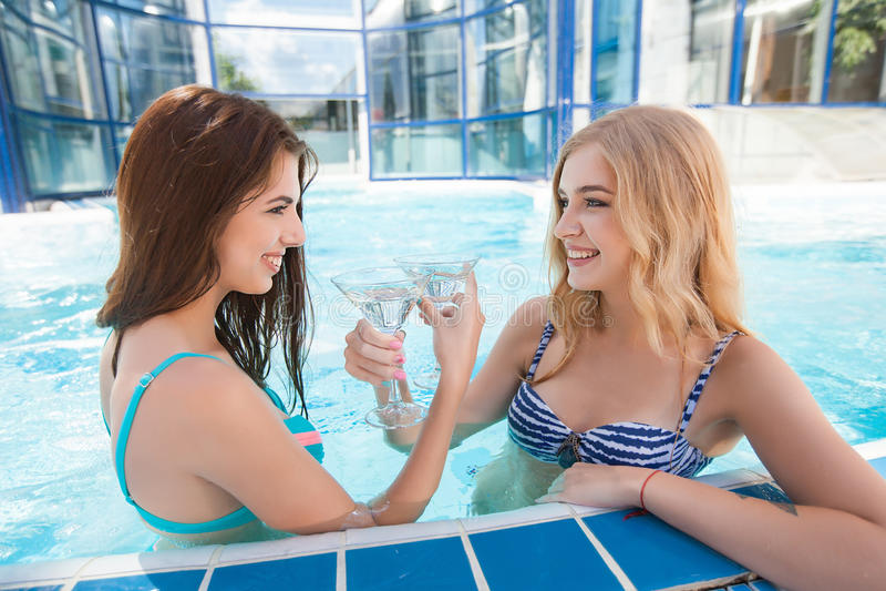 Dos mujeres que disfrutan de vacaciones de verano con los cócteles por la piscina foto de archivo libre de regalías