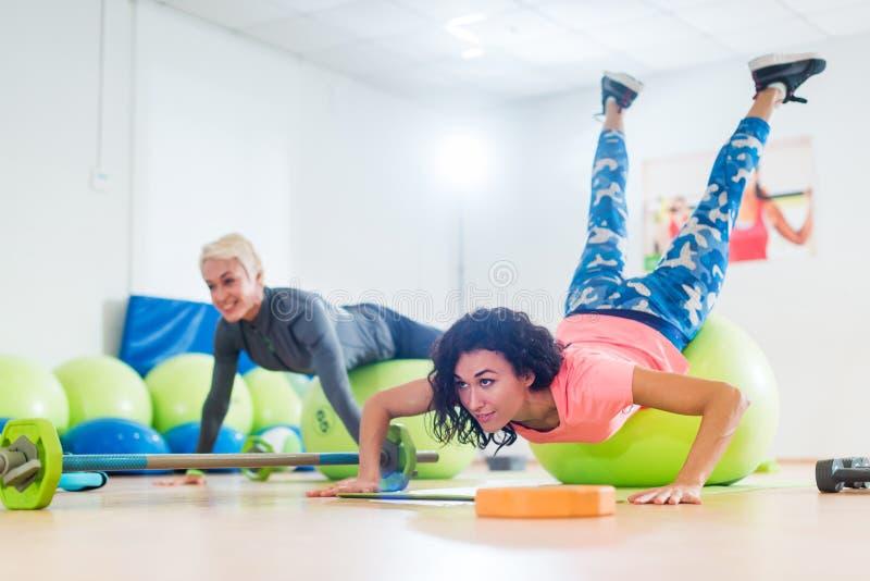 Dos mujeres que ejercitan con las bolas de la estabilidad que hacen pectorales en una clase del gimnasio imagen de archivo