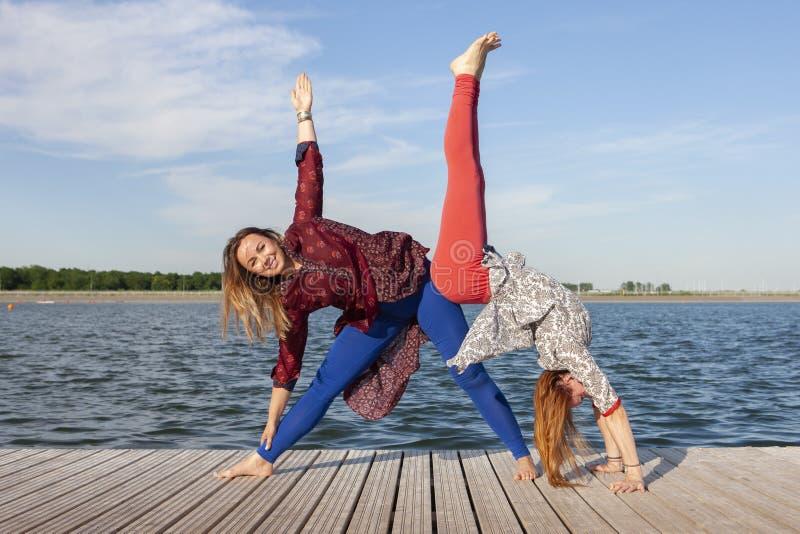 Dos mujeres que ejercitan en el parque Mujer hermosa joven que hace ejercicios juntos al aire libre imagen de archivo libre de regalías