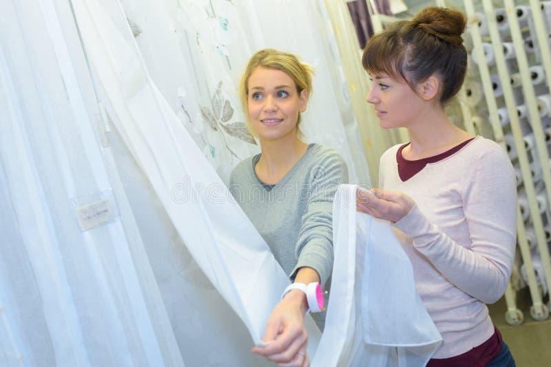 Dos mujeres que eligen la cortina en supermercado imagen de archivo libre de regalías