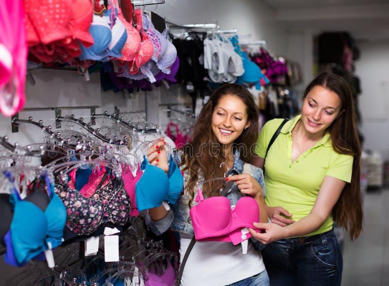 Dos mujeres que eligen la ropa interior en tienda fotos de archivo libres de regalías