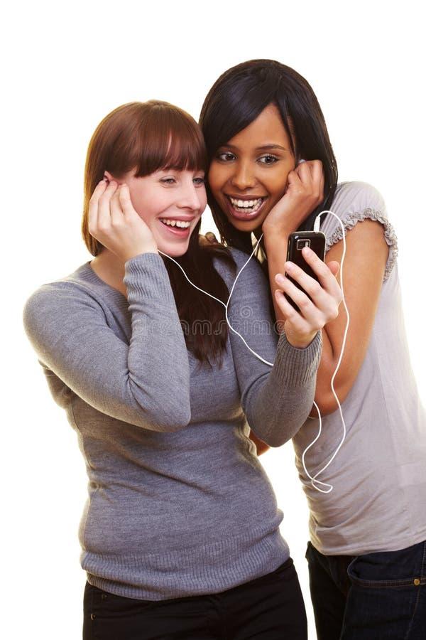 Dos mujeres que escuchan el teléfono celular fotos de archivo libres de regalías