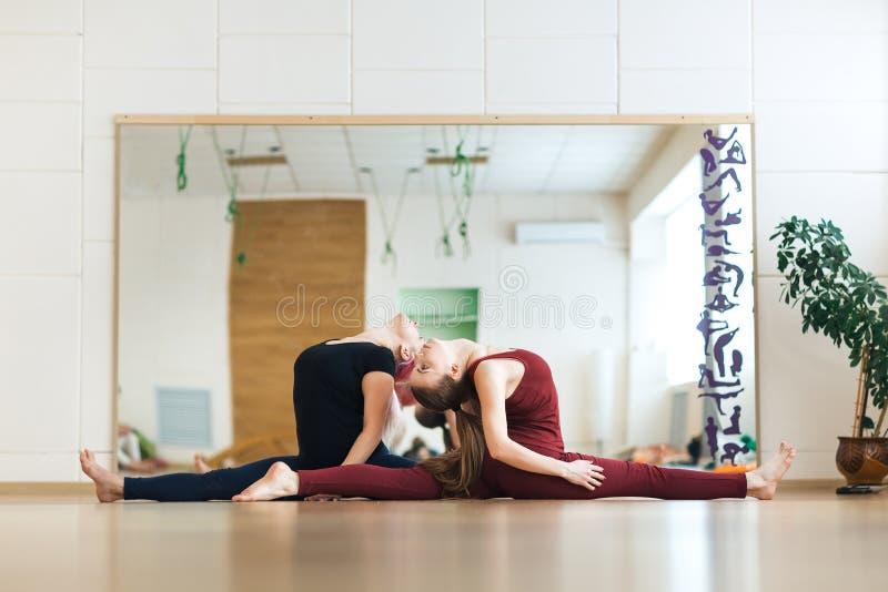 Dos mujeres que estiran yoga o los pilates ejercitan con la variación de las fracturas y del backbend de la pierna de dios del mo imagen de archivo