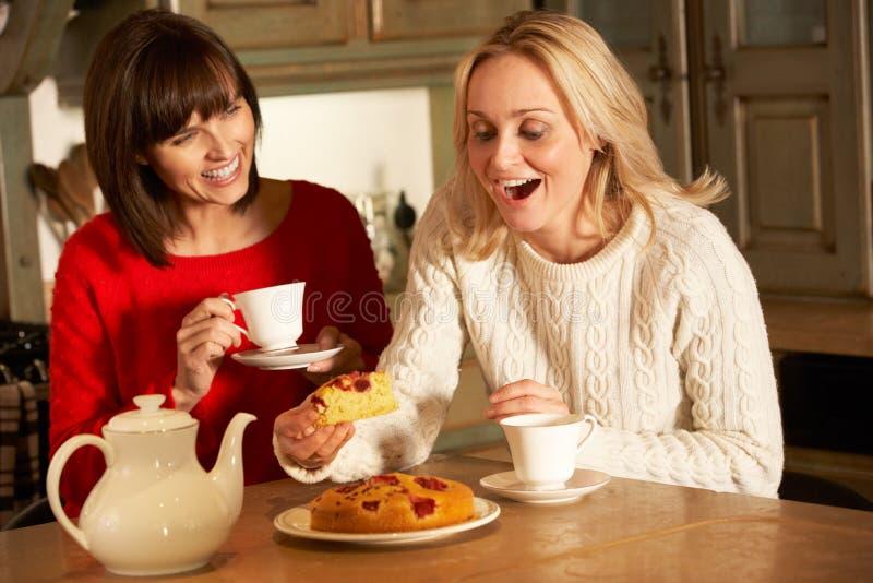 Dos mujeres que gozan de té y de la torta junto fotografía de archivo