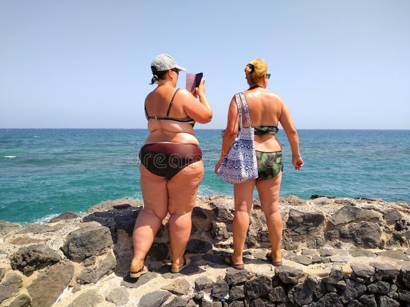 dos mujeres que llevan el bikini y las gafas de sol en una pared de piedra negra cerca del mar que lleva una imagen con un tel?fo fotos de archivo libres de regalías