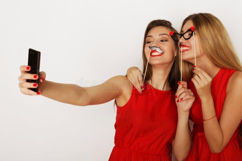 Dos mujeres que llevan el vestido rojo que toma el selfie imágenes de archivo libres de regalías