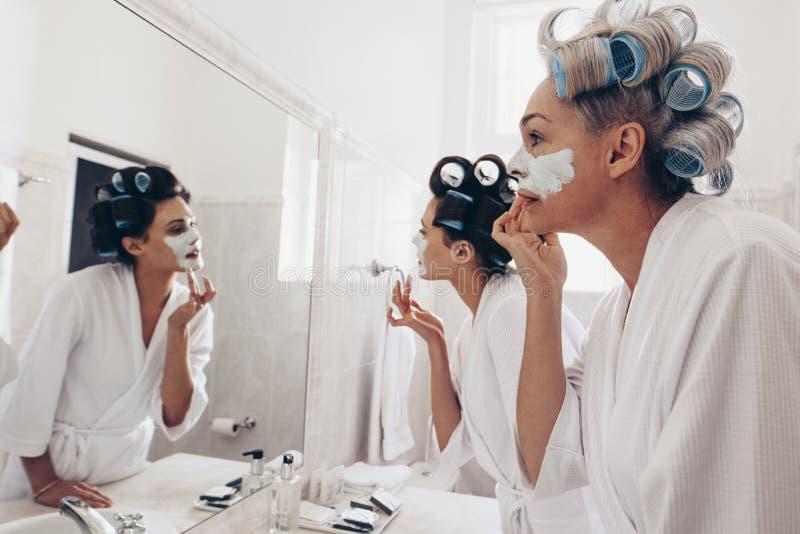 Dos mujeres que llevan las albornoces que aplican la crema en la cara que se coloca en f fotos de archivo