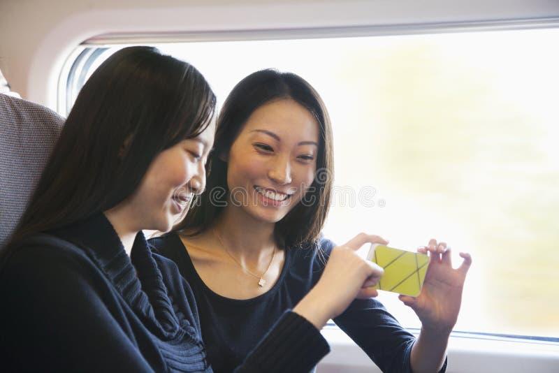 Dos mujeres que miran el teléfono móvil en un tren fotografía de archivo libre de regalías