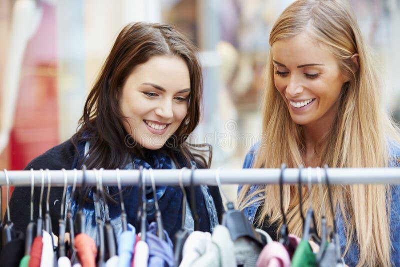 Dos mujeres que miran la ropa en el carril en alameda de compras fotos de archivo
