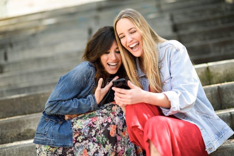 Dos mujeres que miran una cierta cosa divertida en su teléfono elegante imagenes de archivo