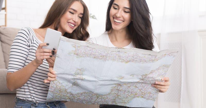 Dos mujeres que planean viaje de las vacaciones con el mapa imagen de archivo libre de regalías