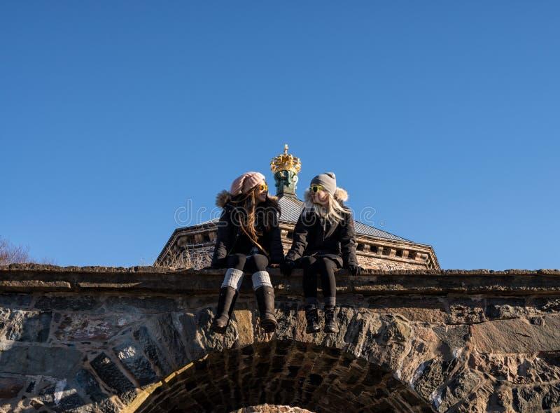 Dos mujeres que presentan en los turistas de las mujeres que presentan debajo de la fortaleza de Skansen Kronan de Goteburgo, Swe imagen de archivo