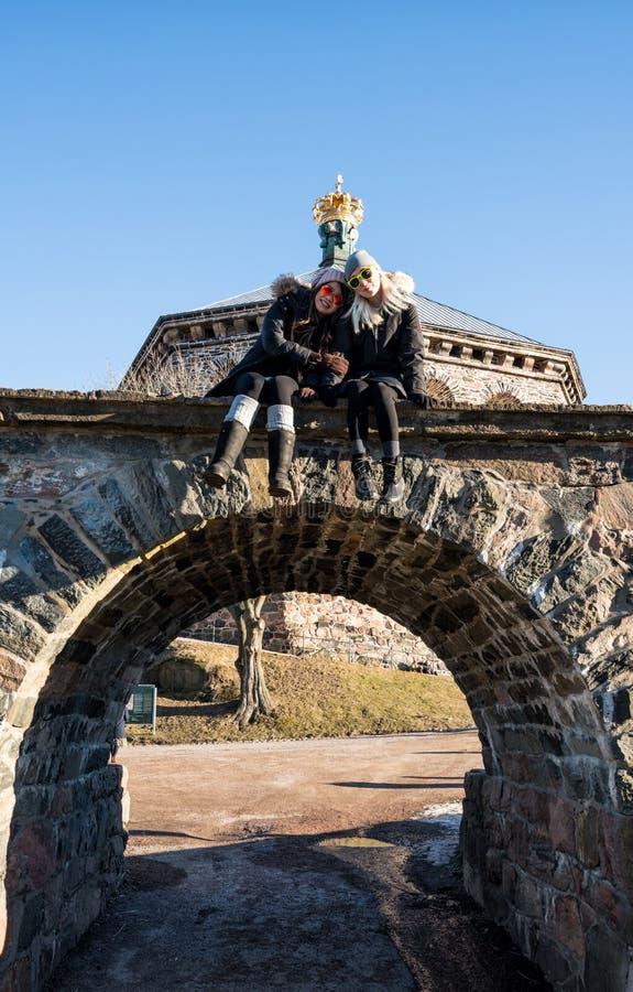 Dos mujeres que presentan en los turistas de las mujeres que presentan debajo de la fortaleza de Skansen Kronan de Goteburgo, Swe imagenes de archivo