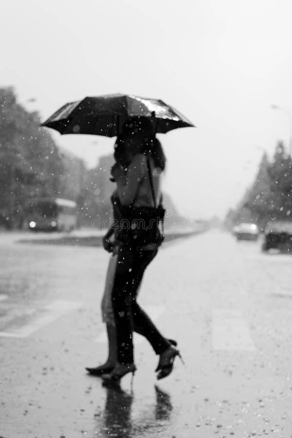 Dos mujeres que recorren bajo la lluvia foto de archivo