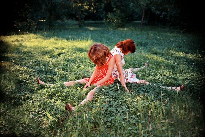 Dos mujeres que se sientan en la hierba fotografía de archivo libre de regalías