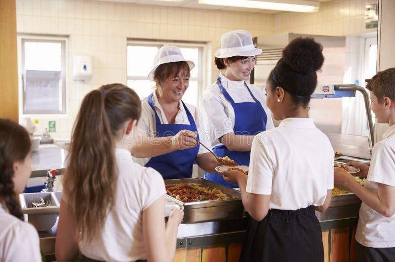 Dos mujeres que sirven a niños la comida en una cafetería de la escuela, visión trasera fotografía de archivo