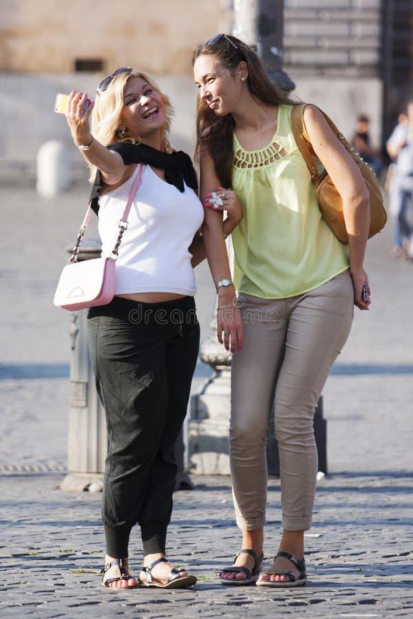 Dos mujeres que sonríen haciendo un selfie con el teléfono imagenes de archivo