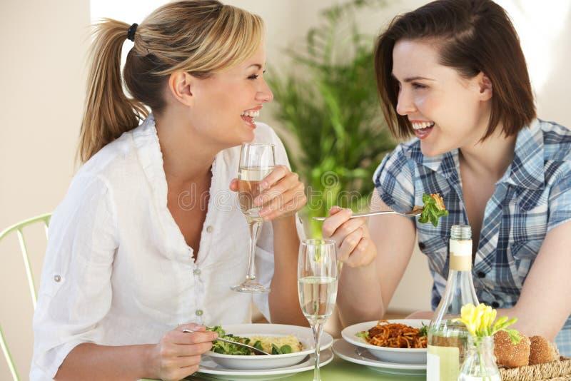 Dos mujeres que tienen comida en café fotografía de archivo libre de regalías
