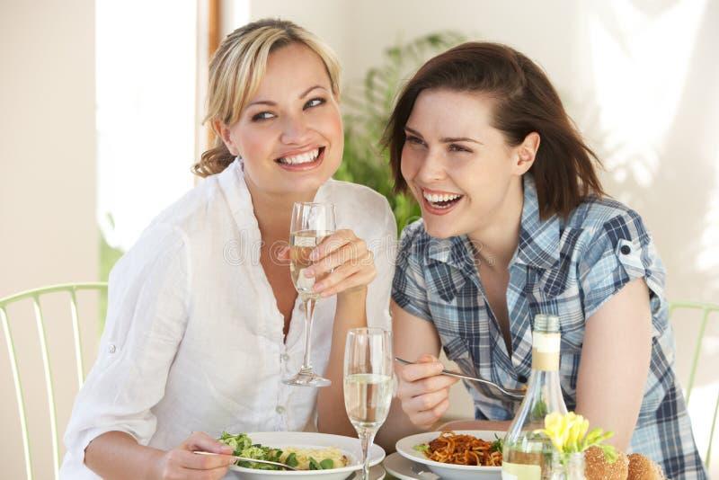 Dos mujeres que tienen comida en café imagenes de archivo
