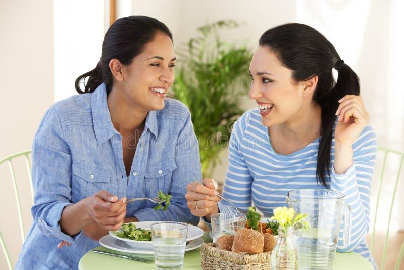Dos mujeres que tienen comida en café fotografía de archivo