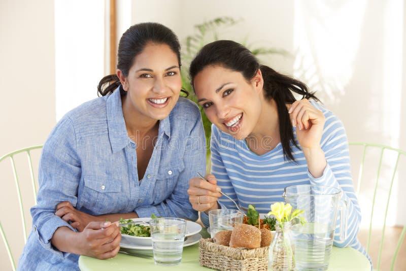 Dos mujeres que tienen comida en café imagen de archivo libre de regalías