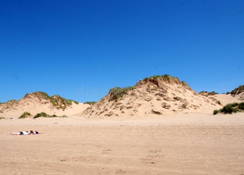 Dos mujeres que toman el sol en la playa con la hierba en el top de dunas de arena altas en la costa del sefton en Merseyside con imágenes de archivo libres de regalías
