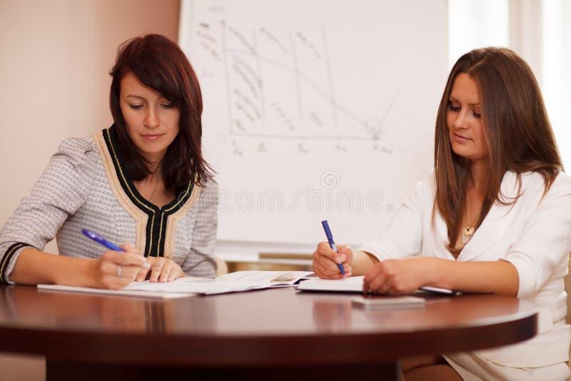 Dos mujeres que toman notas en una presentación del negocio fotografía de archivo