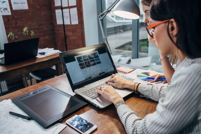 Dos mujeres que trabajan en nuevo sitio web diseñan elegir imágenes usando el ordenador portátil que practica surf Internet fotos de archivo libres de regalías