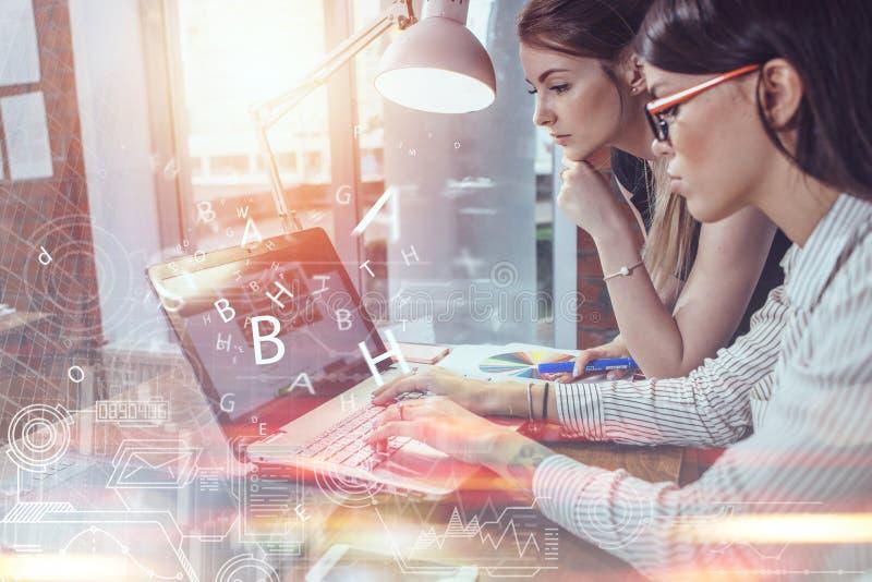 Dos mujeres que trabajan en nuevo sitio web diseñan elegir imágenes usando el ordenador portátil que practica surf Internet imagenes de archivo