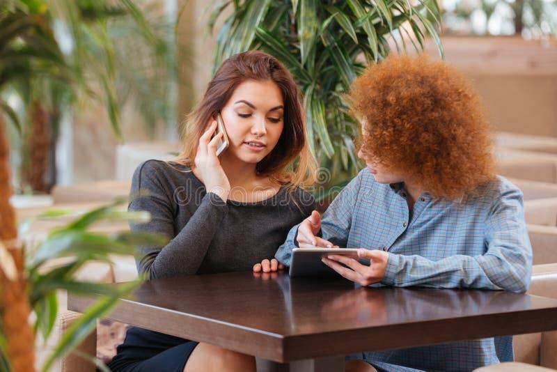 Dos mujeres que usan smartphone y la tableta en café junto fotografía de archivo