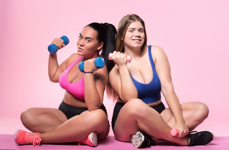 Dos mujeres regordetas que presentan con pesas de gimnasia en piso foto de archivo