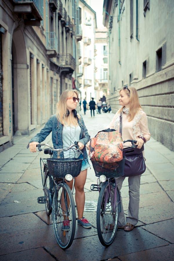 Dos mujeres rubias hermosas que hacen compras en la bici foto de archivo libre de regalías