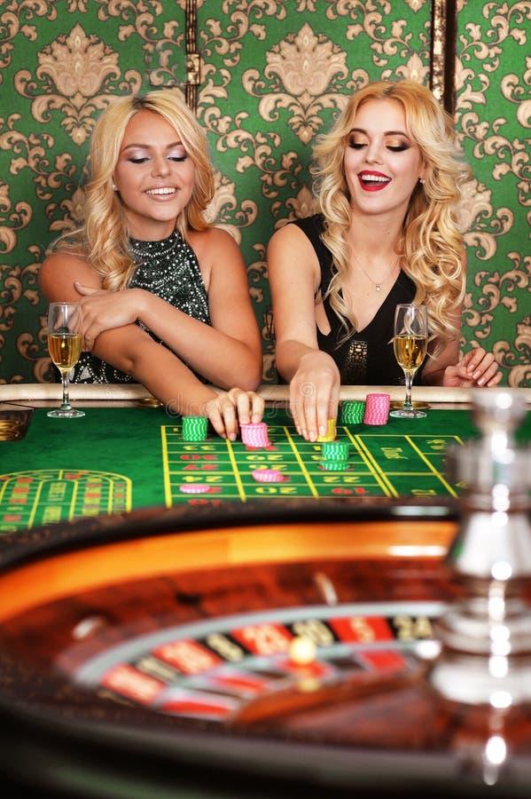 Dos mujeres rubias que juegan la ruleta en casino fotos de archivo