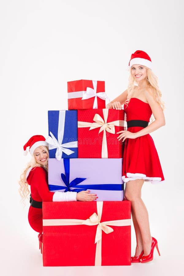 Dos mujeres rubias sonrientes hermosas que colocan y que abrazan presentes coloridos fotografía de archivo libre de regalías