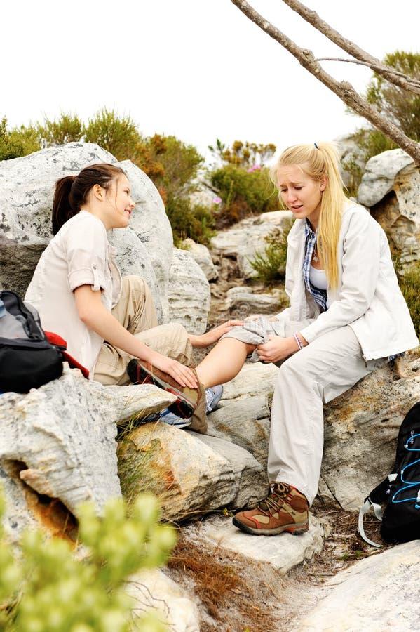 Dos mujeres se ayudan después de que uno de ellos las caídas imagen de archivo