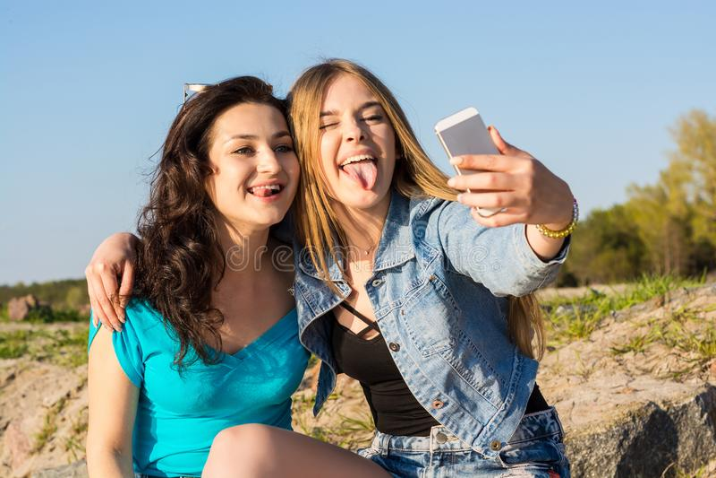 Dos mujeres, se pegan hacia fuera la lengua y hacen el selfie en el aire abierto imagen de archivo libre de regalías