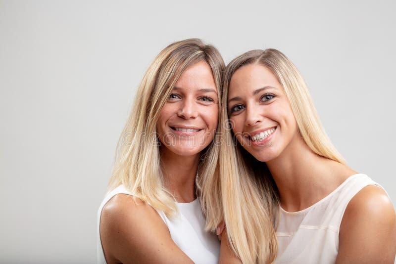 Dos mujeres sonrientes felices con el pelo rubio largo imágenes de archivo libres de regalías