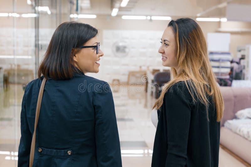 Dos mujeres sonrientes hermosas adultas en perfil, hembras que hablan primer, fondo dentro imágenes de archivo libres de regalías