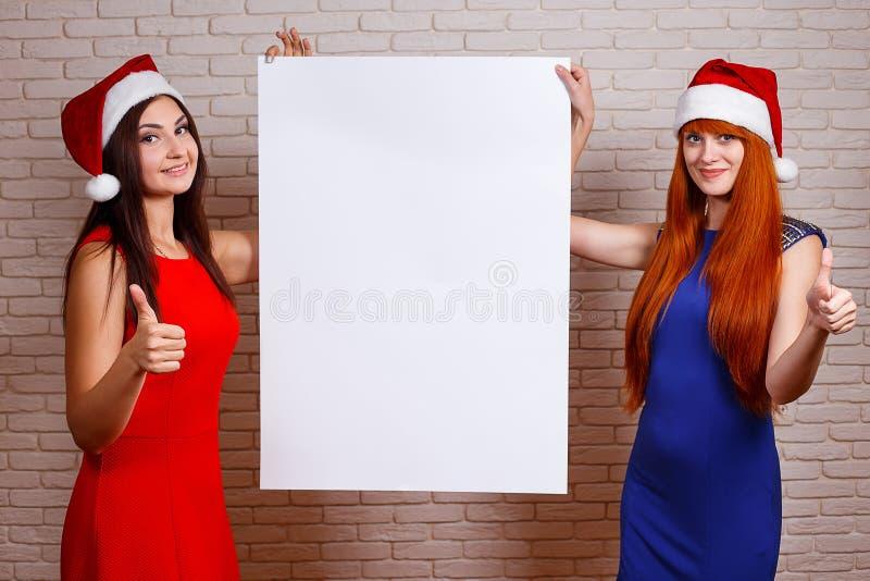 Dos mujeres sonrientes hermosas en los casquillos de Papá Noel con el pulgar encima del gesto fotografía de archivo