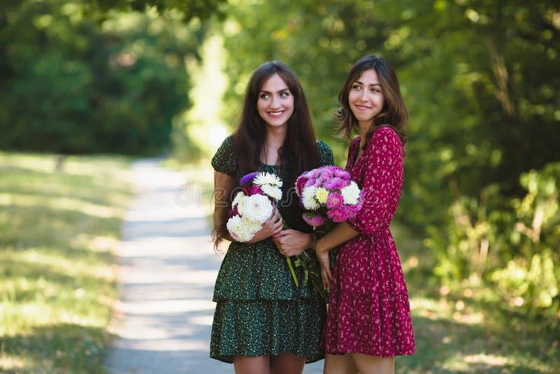 Dos mujeres sonrientes jovenes con las flores foto de archivo