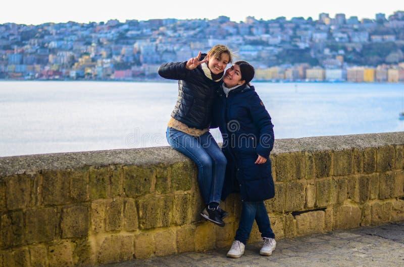 Dos mujeres sonrientes jovenes en el fondo de la ciudad en la puesta del sol ‹Azul del †del ‹del †del mar en el fondo imagenes de archivo