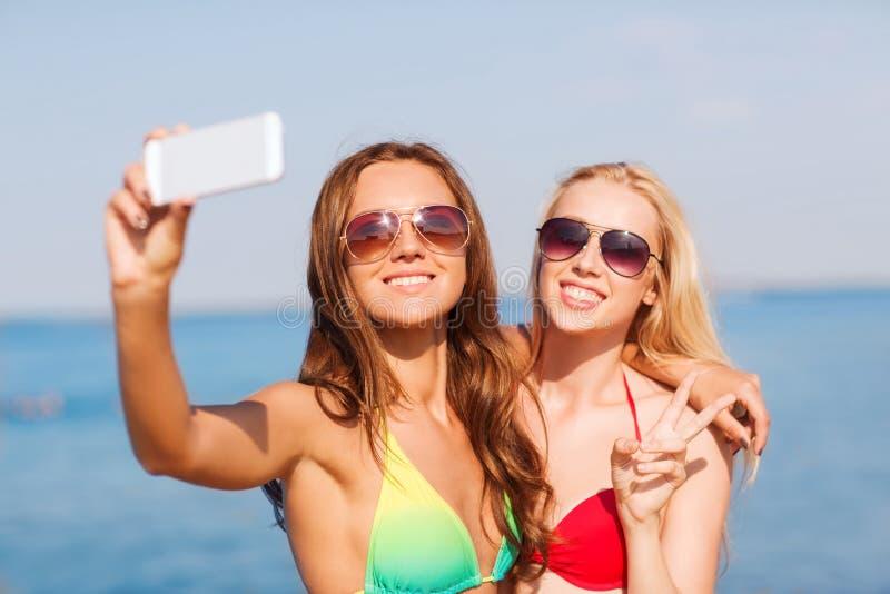 Dos mujeres sonrientes que hacen el selfie en la playa imagen de archivo libre de regalías