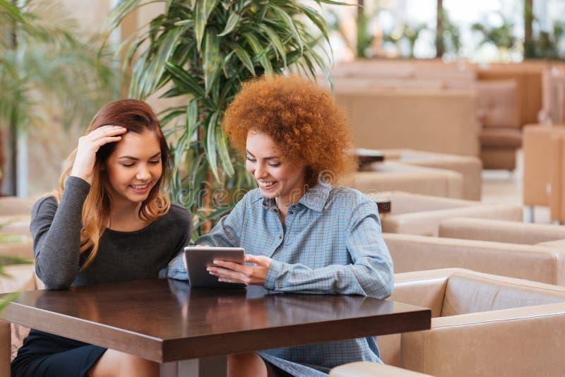 Dos mujeres sonrientes que se sientan en café y que usan la tableta junto imagenes de archivo