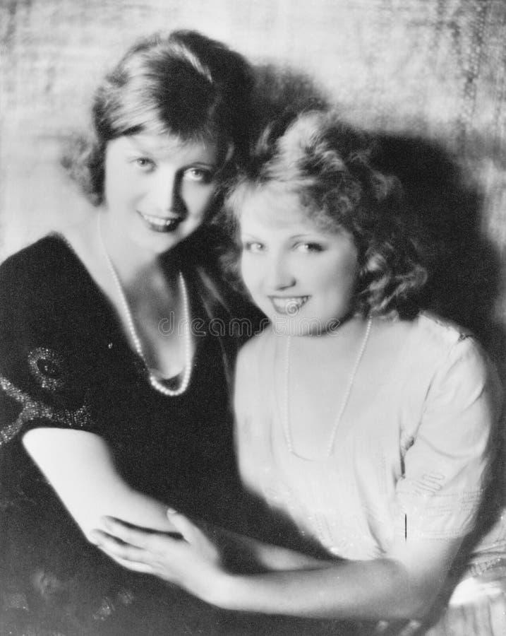 Dos mujeres sonrientes que se sostienen encendido el uno al otro (todas las personas representadas no son vivas más largo y ningú imagen de archivo libre de regalías