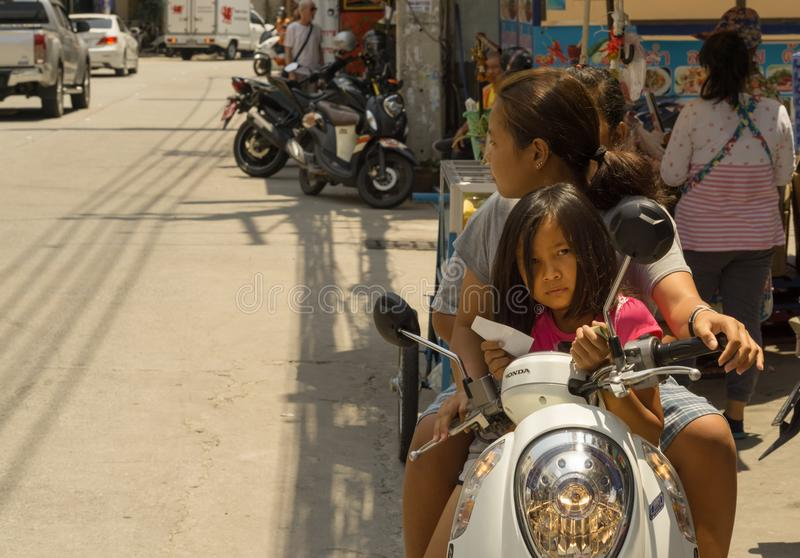 Dos mujeres tailandesas con una pequeña muchacha utilizaban una moto fotografía de archivo libre de regalías
