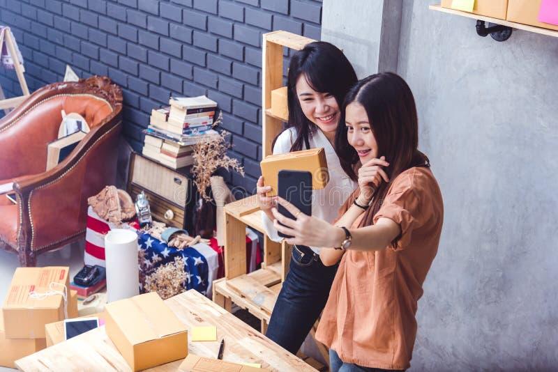 Dos mujeres tomaron un selfie por el teléfono móvil mientras que vendían en línea juntas Negocio y concepto de las formas de vida foto de archivo libre de regalías