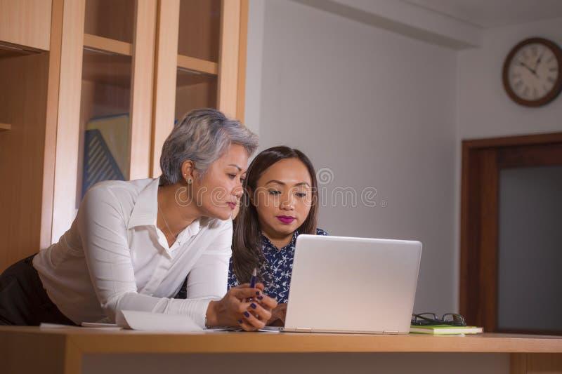Dos mujeres trabajan los colegas o a los socios comerciales que trabajan juntas la lectura en el ordenador portátil en la coopera imagenes de archivo