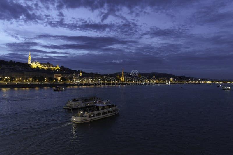 Dos naves se mueven lejos en el Danubio como pasa a través de Budapest con el bastión de los pescadores y la orilla iluminada d imagen de archivo