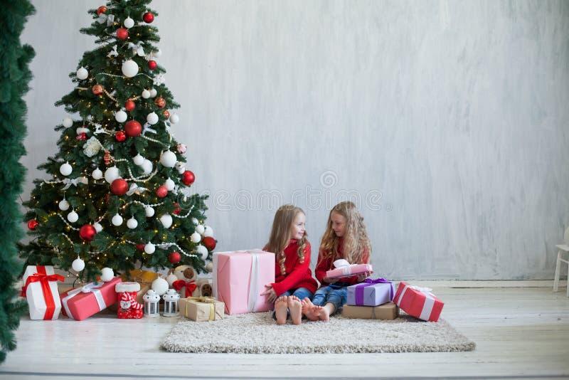 Dos niñas abren los regalos de la Navidad en la casa de vacaciones del Año Nuevo del árbol de navidad imagen de archivo libre de regalías